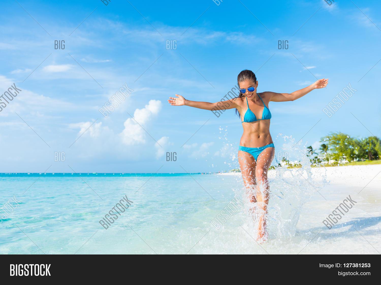 f870a80c247f2 Freedom carefree girl playing splashing water having fun on tropical beach  vacation getaway travel holiday destination