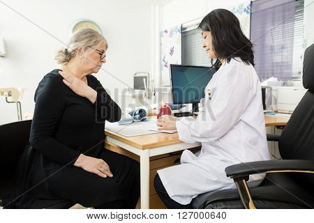 Doctor Explaining Anatomy To Senior Patient Suffering From Shoul