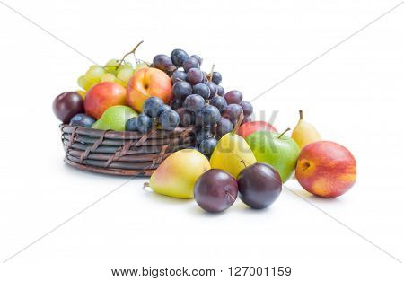Mix of various fresh ripe fruits plums apples pears peaches and grapes placed in a wicker basket and around isolated on a white background.