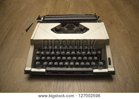 Old gray typewriter on brown wooden floor