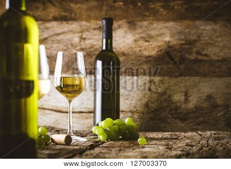 Wine. Glass of white wine in wine cellar. Old white wine on wood.