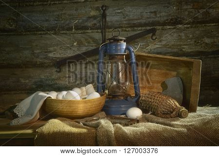 Still life with kerosene lamp, a trough and a bowl of eggs in an old storeroom