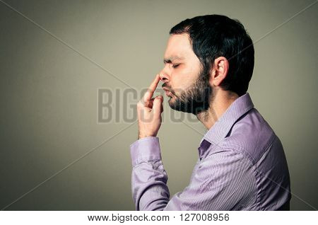 man with the beard touching his nose