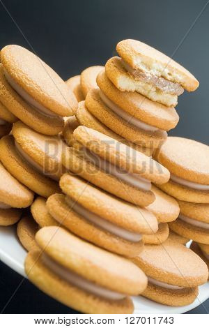 Sweet sandwich biscuits filled with hazelnut cream arranged in a pyramid pile in white plate with one bitten biscuit on top close up on dark neutral background.