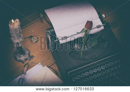 Antique typewriter on a desk and a candle