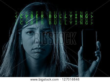 young scared and worried teenager girl holding mobile phone as internet stalked victim abused and cyberbullying or cyber bullying stress concept in computer text code black background