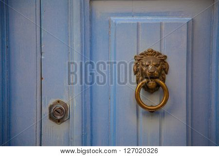 A handmade lionhead doorknob on a cyan wood door with his lock