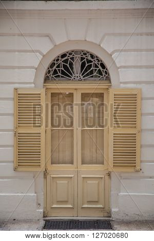 An old weathered french window with opened shutters