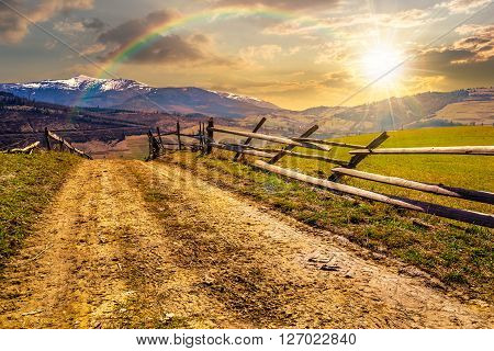 carpathian mountain peaks in snow above green rural meadow near the road with wooden fence in evening light