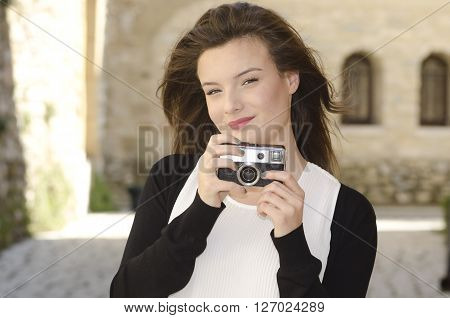 beautiful young girl with an old camera in his hands