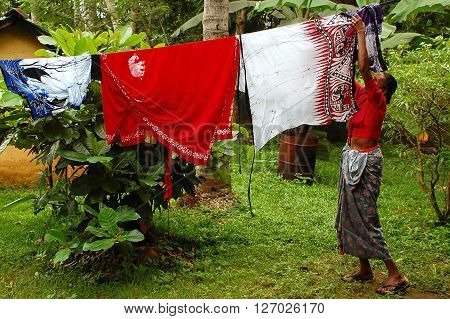 KANDY S,RI LANKA - DECEMBER 5, 2008: An unidentified woman hangs out the laundry to dry in the garden