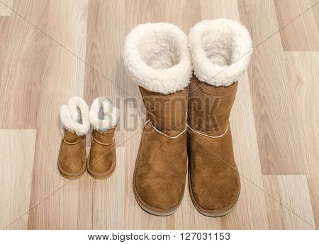 Pair of winter woman boots and similar pair of kid boots. Matching big and small boots.