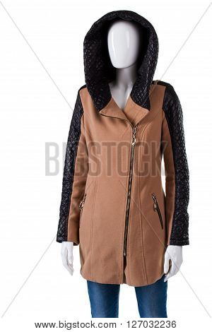 Woman's brown coat with hood. Mannequin in brown hooded coat. Autumn coat with leather inserts. Fashionable outerwear in boutique.
