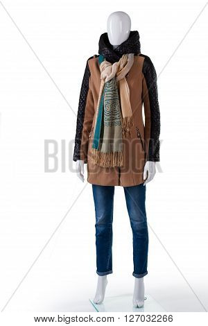Jacket with jeans and scarf. Female mannequin wearing brown jacket. Lady's autumn outerwear with scarf. Fashionable and warm clothing.