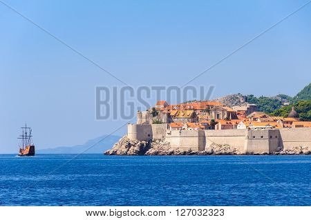 DUBROVNIK CROATIA - AUGUST 31 2009: Old city as viewed from the sea to the east and a galleon sailing ship