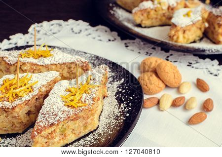 Torta di riso - classical Italian dessert. Rice cake with almonds candied orange peels and amaretto. A slices of rice cake with almond cookies in a plate. Italian food. Selective focus. ** Note: Shallow depth of field