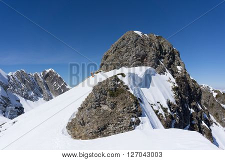 Man with snowboard on top of a mountain, extreme moutaineering.