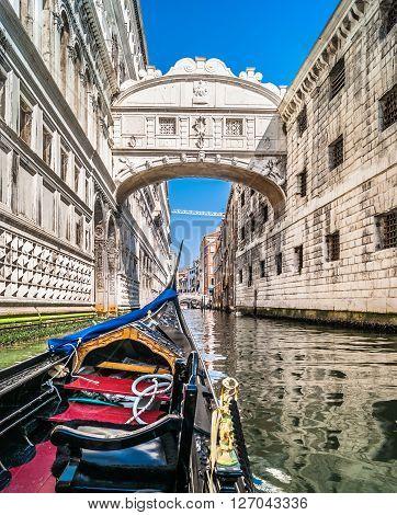 Under the Bridge of Sighs in gondola, legendary historic bridge, one of famous landmarks in Venice, Italy.