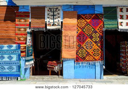 Wall of a local store with traditional Mexican handmade carpets on display