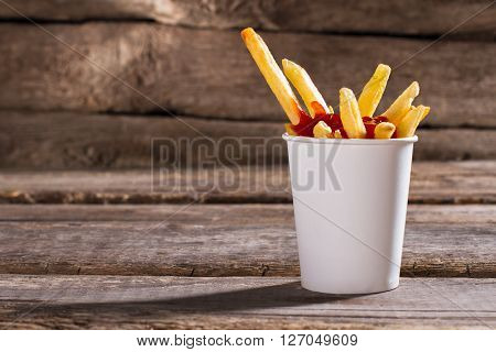 Fries with sauce in cup. French fries with tomato ketchup. Aged table with tasty snack. Popular fast food dish.