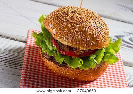 Big burger on napkin. Hamburger with sesame buns. Fresh beefburger on white table. New dish worth tasting.
