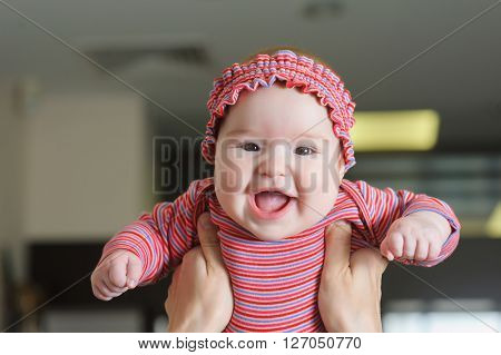 Child smiling mother. Mom raised her child above her head. Happy charming 5-month-old baby girl smiling and grimacing in female hands. Home interior in background.  Mother throws up baby, playing indoors.