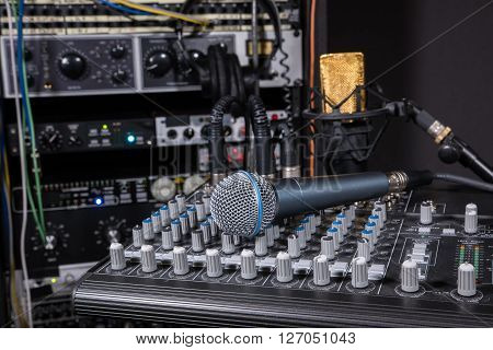 Mixing console and dynamic microphone in recording studio setting.