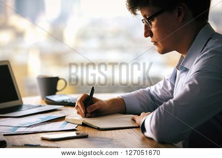 Sideview of businessman writing something down in copybook placed on wooden desktop with notebook business reports smartphone and other items ** Note: Shallow depth of field