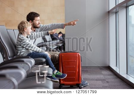 positive smiling boy and his father waiting at the airport for plane departure and pointing with fingers at something vacation and travel concept