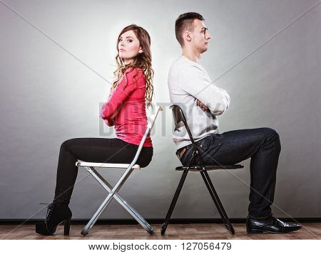 Young couple not talking to each other and sitting back to back after argument quarrel. Disagreement in relationship. Angry man and offended woman get mad.