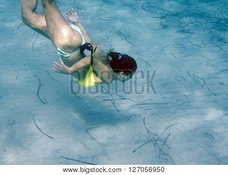 Caucasian girl swimming underwater in Villasimius' sea