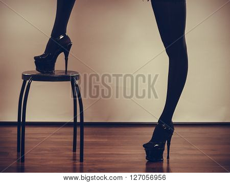 Sexuality of women. Part body woman wearing black sexy stockings. Long female legs in high heels on chair.