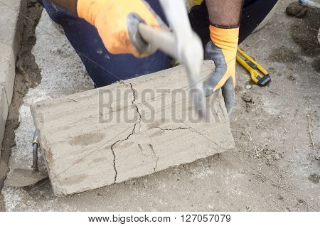 Construction Worker Breaking A Mud Brick With Pick