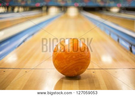 Bowling ball sitting in a colorful bowling alley lane