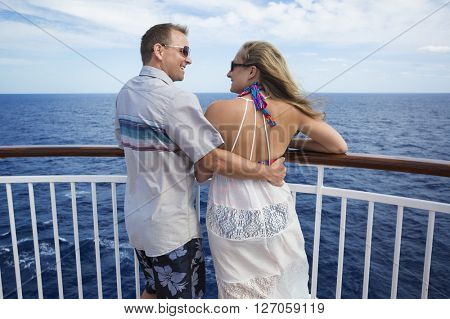 Happy married couple smiling on the balcony of their cruise ship while on vacation together