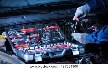 Professional auto mechanic working in repairing service, close-up. Car diagnostics concept