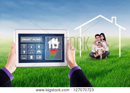 Close up of applications of smart house system controller on the tablet with happy Asian family sitting on the meadow under a house symbol