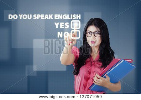 Female college student touching a virtual screen with a text of Do You Speak English