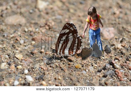 Very little girl and big butterfly. Photo collage.
