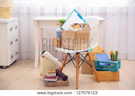 Cardboard and wooden boxes with things for relocation in room interior poster