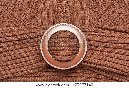 big round fastener button on brown knitted wool pullover macro photo closeup as background