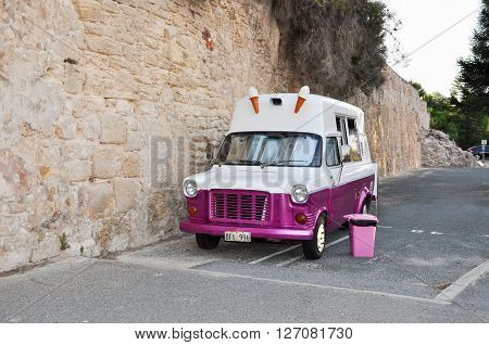 FREMANTLE,WA,AUSTRALIA-JANUARY 26,2016: Vintage pink and white ice-cream truck outside limestone wall at the Whaler's Tunnel in Fremantle, Western Australia.