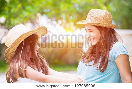 Portrait of a joyful young mother with her cute cheerful daughter wearing same straw hats and playing outdoors, laughing and looking on each other, portrait of a happy family enjoying life