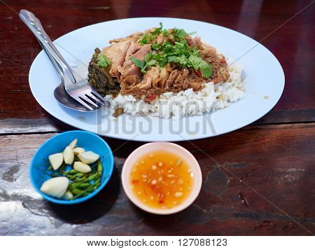 A bowl of rice with pork knuckle meat served with side dish such as green chili garlic and sweet chili sauce. Served in a Thai casual restaurant with fork and spoon.