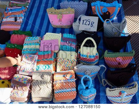 An assortment of colorful woven bags for sale by a street vendor. These bags are handmade with a cheap price tag.