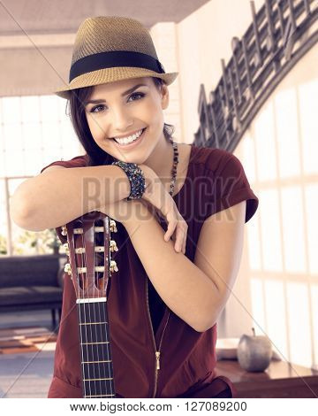 Happy young woman smiling at camera, leaning on guitar.