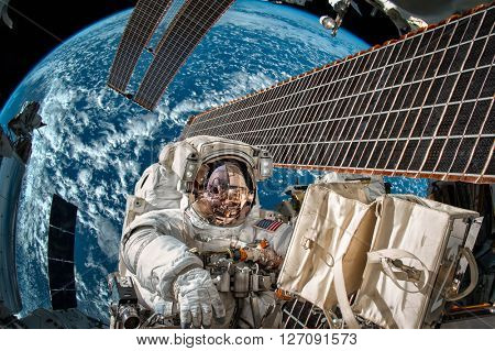 International Space Station and astronaut in outer space over the planet Earth. Elements of this image furnished by NASA. poster