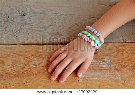 Child wears bracelets on his hands. Child hand wearing bracelets. Bracelets from plastic beads. Old wooden background