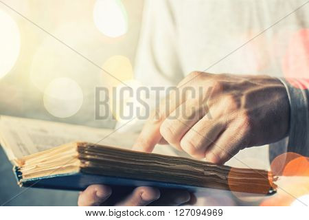 Man reading old book with torn pages close up of adult male hands holding vintage book bokeh light in background.