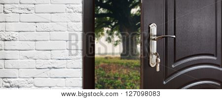 Entrance door half opened to nature background. Door handle, door lock. Exit outdoors. Opening door. Entrance to the house. Door at white brick wall, summer field and tree, freedom concept.